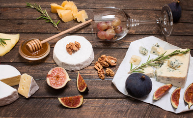 Cheese selection on wooden rustic board. Cheese platter with different cheeses, grapes, nuts, honey and figs on weathered wood background.