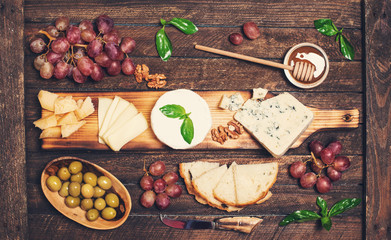 Cheese board. Various types of cheese. Cheese plate with cheeses Parmesan, Brie, Camembert and Roquefort  serving with grapes, honey, nuts, olives  and bread on wooden board.