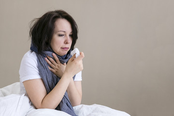Young girl sick in bed with temperature. runny nose, cough, stay home