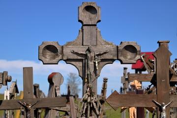 Drewniany krzyż z wizerunkiem ukrzyżowanego Chrystusa, w tle nieostrych wiele innych krzyży, drewnianych i metalowych, prostych, przekrzywionych, w plenerze, w tle nieostre drzewo, błękitne niebo