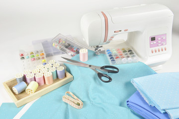 Sewing machine and colorful thread rolls, scissors, fabric and accessories for sewing on white background, Sewing and needlework concept. (Selective Focus)