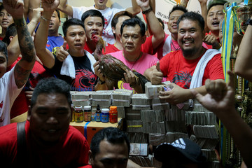 The owner of the winner rooster and his team pose after winning a cockfighting match with the highest cash reward of cockfighting in Thai history for more than one million USD at a stadium on the outskirts of Bangkok