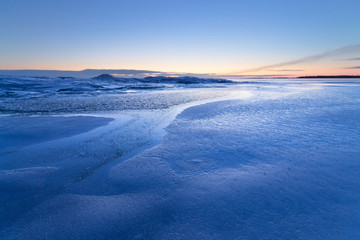 a cold blue winter morning / the shore of a frozen lake dawn