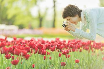 花畑で写真を撮る若い女性