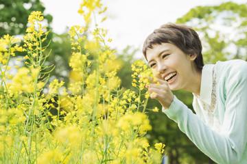 菜の花畑を散歩する女性