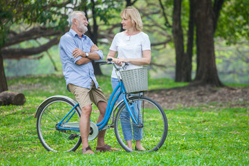 happy Senior Couple  in a park with a bicycle