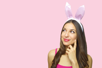 Attractive young woman with bunny ears looking to the side thinking or desire your product isolated on pink background. Copy space.