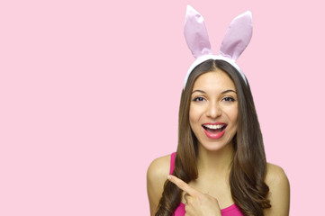 0ea99966336 Attractive cheerful girl with bunny ears pointing your product or logo  isolated on pink background.