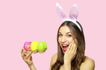 Happy surprised woman with bunny ears holdings egg carton of colorful Easter eggs looking at camera over pink background. Copy space.