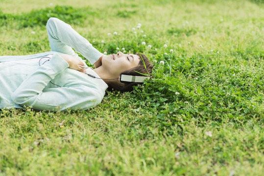 公園の芝生でスマホを使う女性