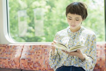 電車で読書をする女性