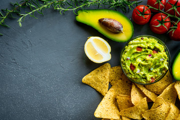 Guacamole bowl with ingredients and tortilla chips on a stone table. Top view image. Copyspace for your text.