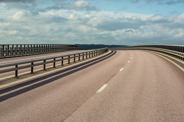 highway curve against cloudy sky background