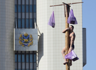 A man holds a prize as he climbs up a wooden pole during Maslenitsa celebrations, a pagan holiday marking the end of winter, in Vladivostok