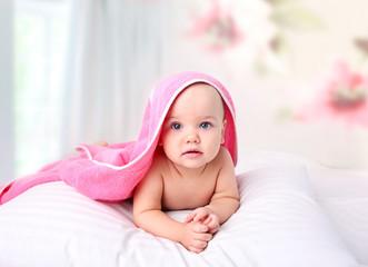 Baby in towel lying in bed.