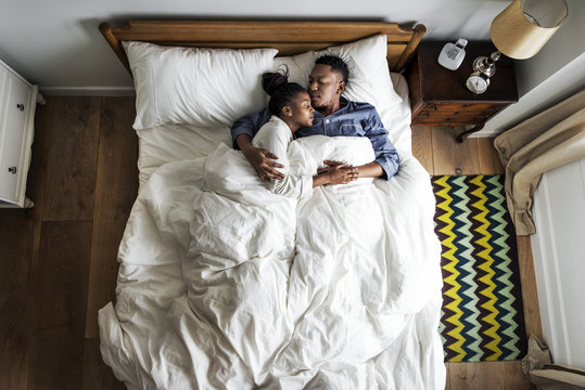 Lovely African American couple snuggling in bed