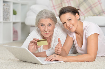 Mother and her adult daughter using laptop