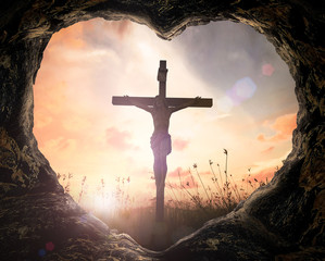 Good Friday concept: Heart shape of cave with Jesus Christ on cross over meadow sunset background.