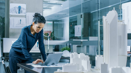 Female Architectural Designer Works on a Laptop,  Engineering New Building Model for the Urban Planning Project. Clean Minimalistic Office, Concrete Walls Covered by Blueprints and Documents. Fototapete