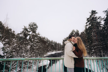Loving couple in a pine forest in winter