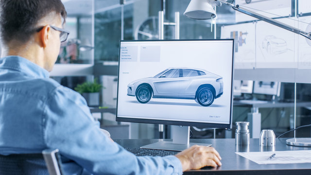 Automotive Engineer Works on the Personal Computer, He Perfects New Car Model Prototype Sketch. He Works in the Bright and Modern Office.