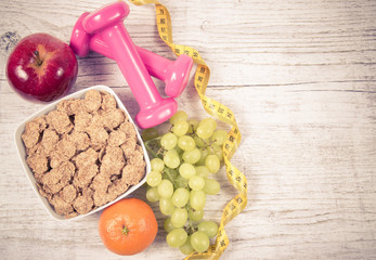 Diet fitness concept - dumbbells, measuring tape, flakes and fresh fruits on wooden table.