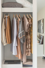 wooden wardrobe with clothes hanging on rail