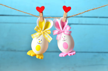 Easter eggs hanging on rope on blue background