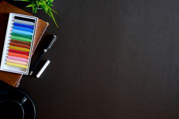 Designer workspace top view with essential elements on dark wooden board.