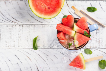 Watermelon slices in a blue porcelain cup on white wooden table