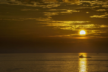 Burning sky in the ocean with single boat
