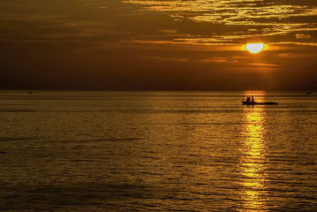 Golden hours in ocean with boat under sun light.