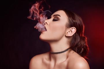 Glamour seductive gorgeous brunette woman smoking electronic cigarette