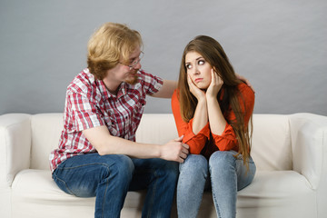 Woman confiding to man on sofa
