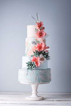 Wedding four-tiered cake decorated with spring red flowers and handmade pattern. Concept of delicious desserts