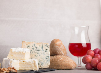 various french cheeses with red wina, grapes,baguette and nuts.