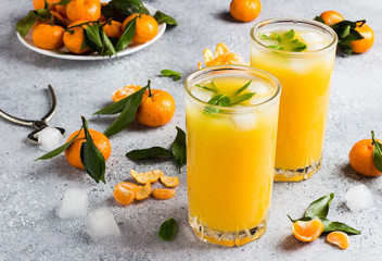 Tangerine juice in glasses on light background