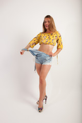young sexy posing lady wearing a yellow top with flowers and blue jeans playing with her dungarees while smiling  into the camera