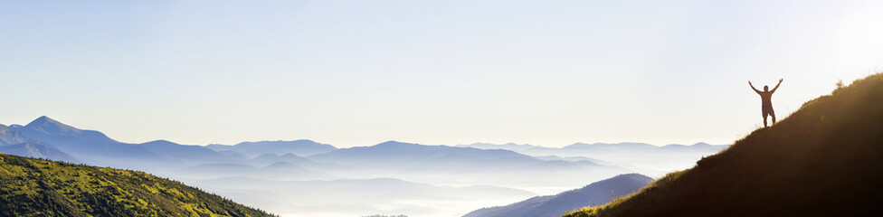 Panorama of young successful man hiker silhouette open arms on mountain peak.