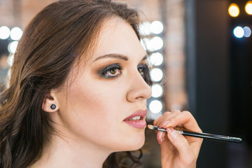 Professional make-up artist applies makeup on young beautiful caucasian woman