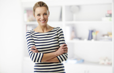 Happy middle aged woman portrait. A confident casual businesswoman standing with arms crossed at the office while looking at camera and smiling.