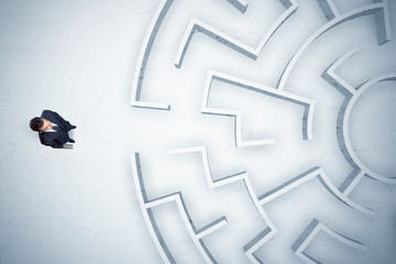 Wall Mural - Business man looking at circular maze with nowhere to go
