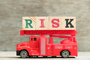 Red fire truck with ladder hold block word risk on wood background