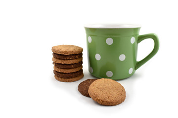 Green mug with dots stock images. Cookies and green mug. Cookies with cup on a white background. Big spotted mug