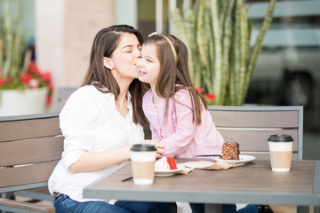 Mother kissing her daughter in the restaurant