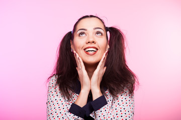 Surprised woman looking up on pink background