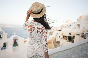 Woman in white dress and straw hat on Santorini island