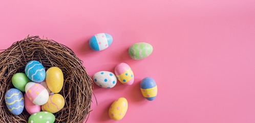 Colorful easter egg and nest on pink pastel color background with space.