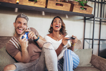 Beautiful couple having fun while playing video games.