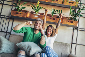 Modern couple looking excited and happy after their favorite football team scored a touchdown